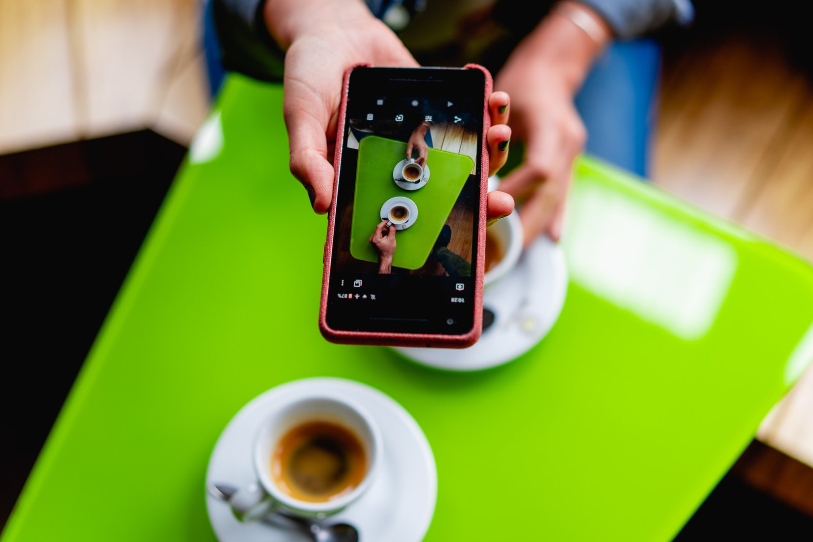 Photo of a cellphone taking a picture of cups of coffee on a green teable