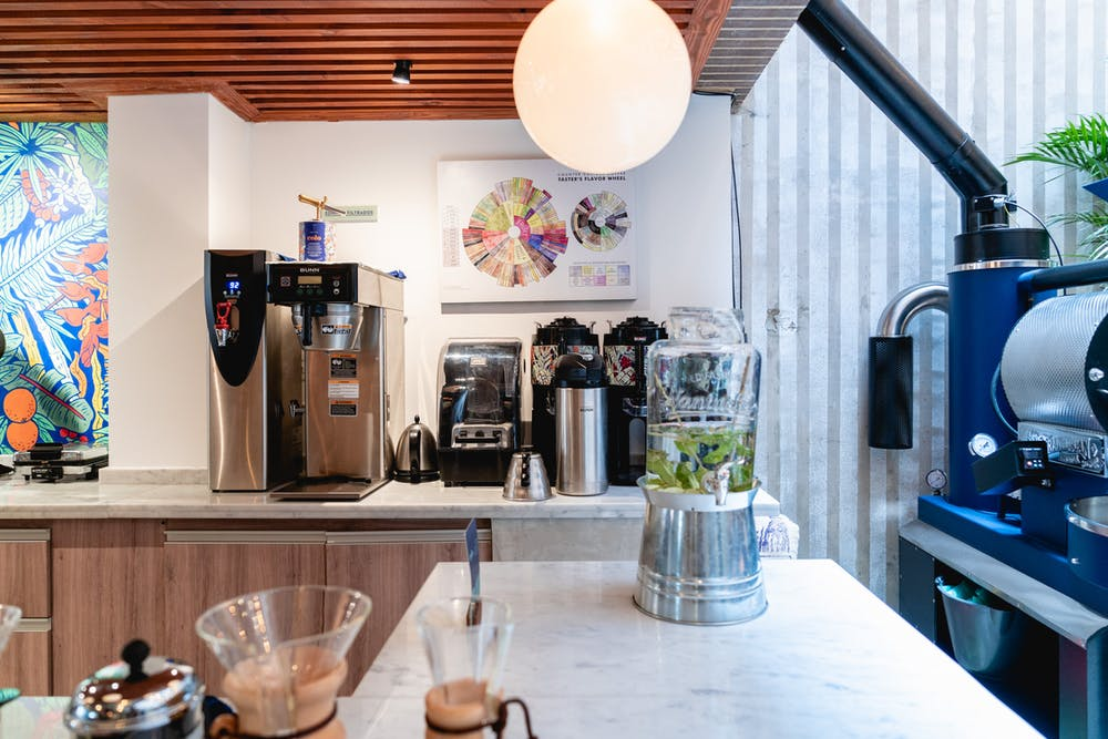 Sleek white coffeeshop interior with silver coffeemakers, wall art and gray marble countertops
