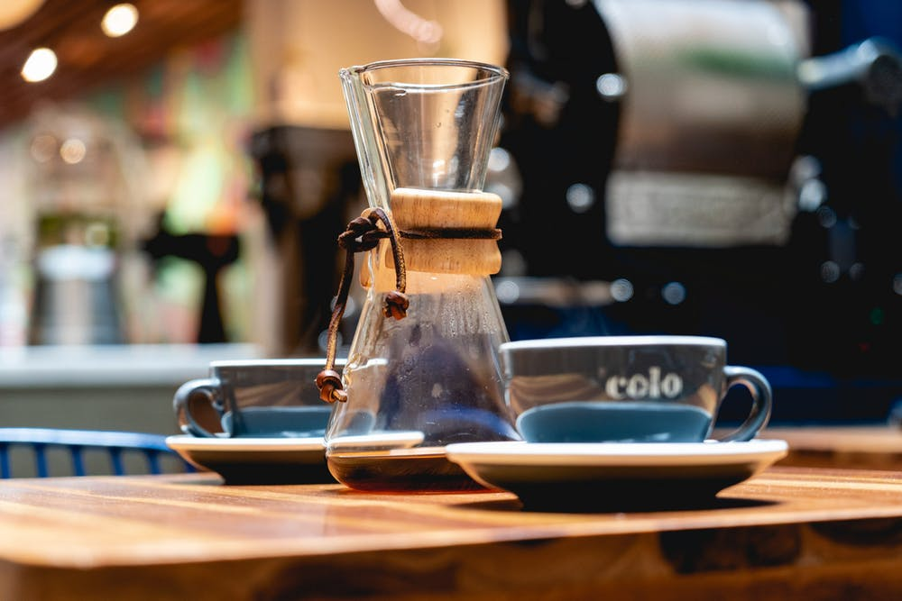 Skinny Chemex glass beaker and two gray coffee cups on a wooden table in a cafe