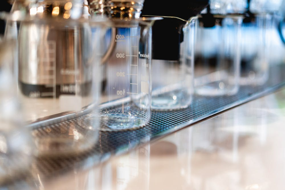 Row of clean clear glass beakers along the bar of a coffeeshop