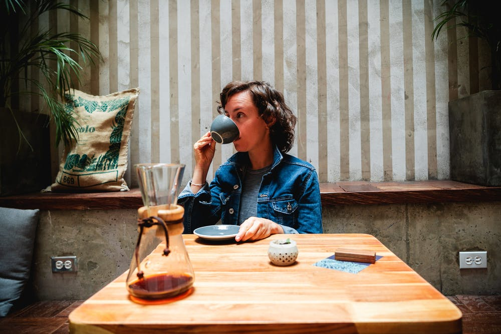 Girl drinking espresso from a cup at a table in a chic coffeeshop