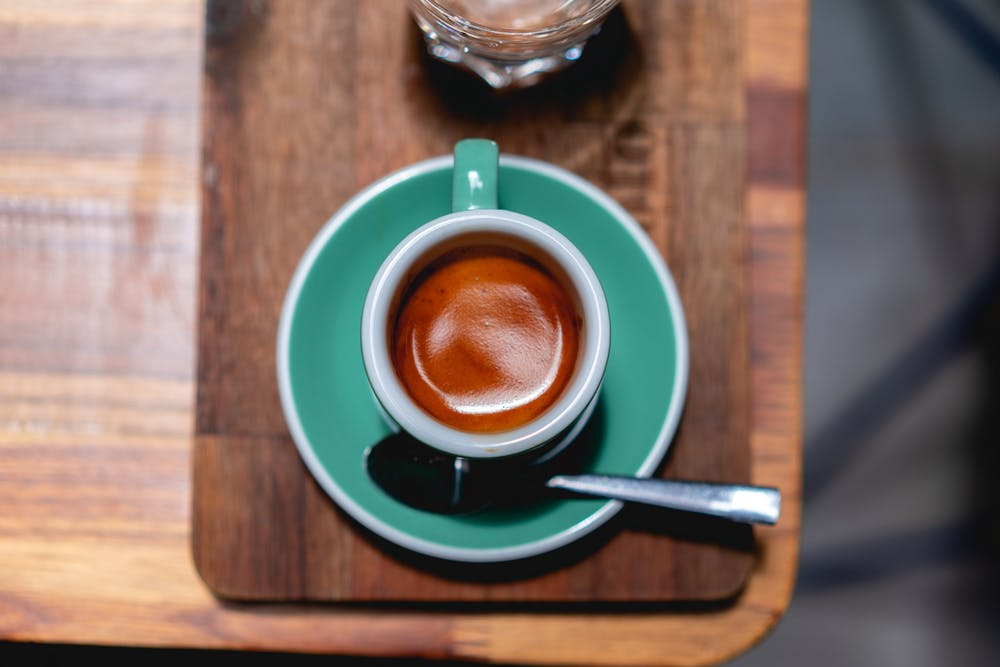 Turquoise saucer and espresso cup filled with espresso on a wooden table in a coffeeshop