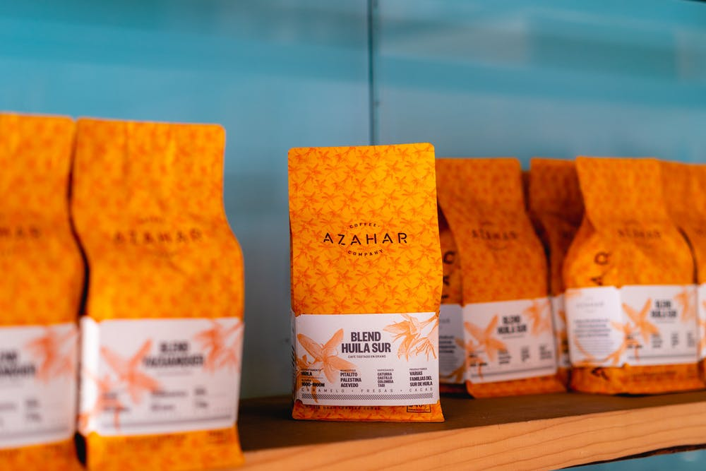 Orange bags of coffee beans for sale against a teal wall at a third wave cafe