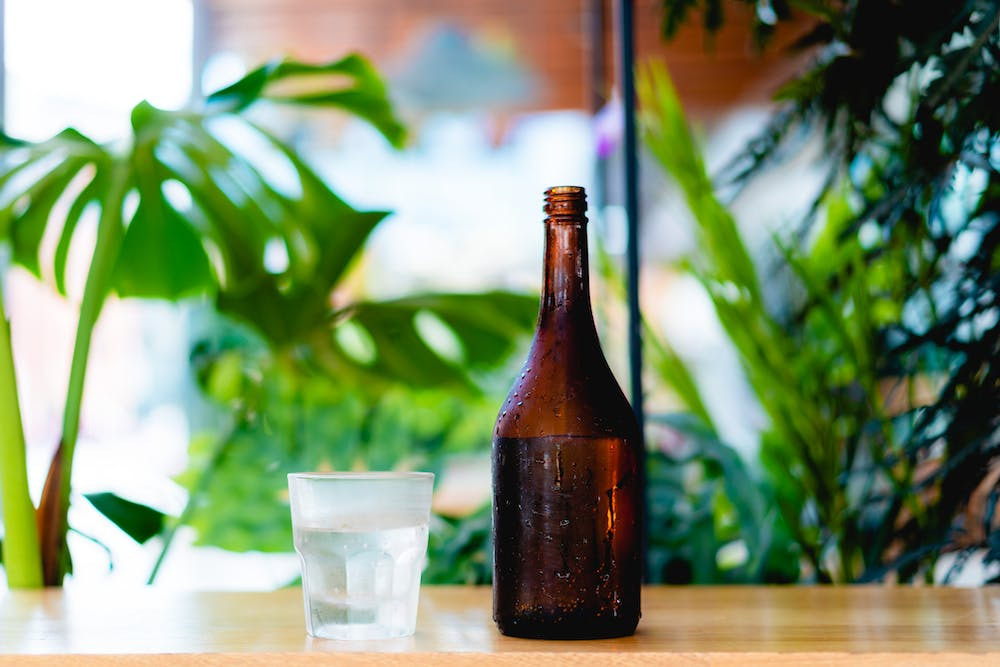 Brown glass bottle with condensation and small short glass of water against natural plants on a wooden ledge