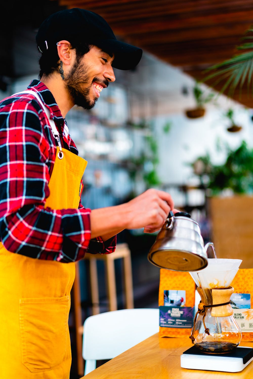 Smiling man wearing a red and black plaid flannel shirt and orange barista apron pouring hot water into a Chemex from a gooseneck kettle