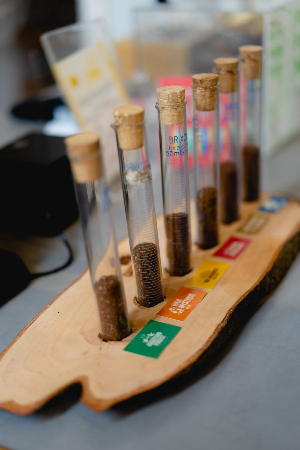 Glass vials with corks of different types of Colombian coffee set in a wooden slab at a cafe