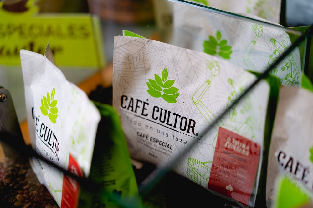 White and green CAFE CULTOR bags of coffee for sale at a Bogota coffeeshop