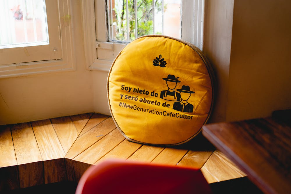 Yellow gold coffee themed Spanish throw pillow in a bay window of a Bogota coffeeshop
