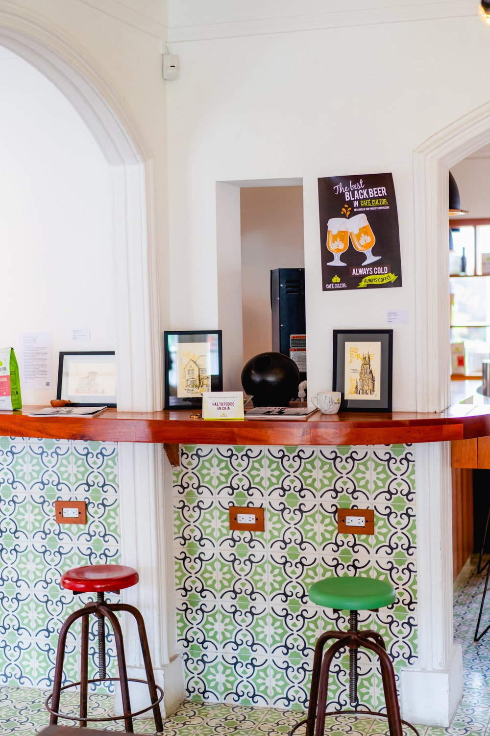 Red and green stools at a coffeeshop bar wit white walls and patterned tiles