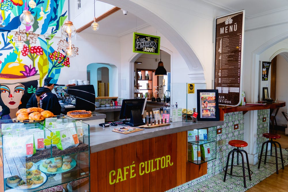 Cafe Cultor interior with painted wall art, white walls, wood panel bar and tiled surfaces, and white archways between rooms of a house