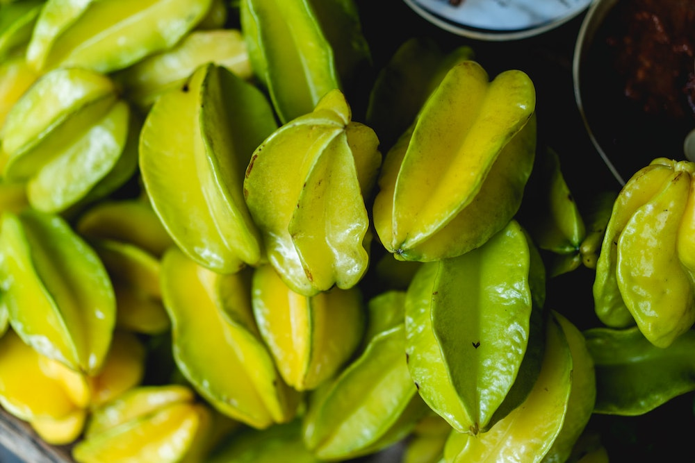Green star fruits for sale in a market in Colombia