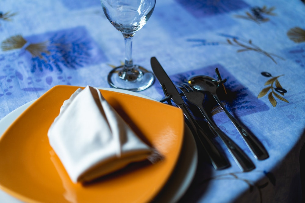 Blue theme place setting with napkin and silverware on tablecloth