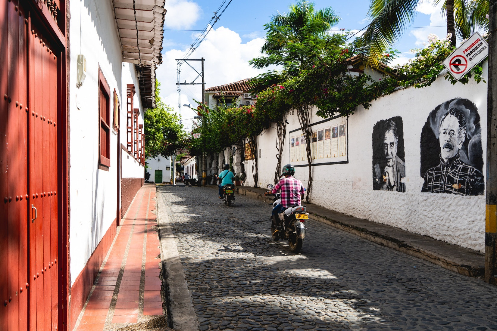 Men on motorcycles driving on cobblestone street in Colombia