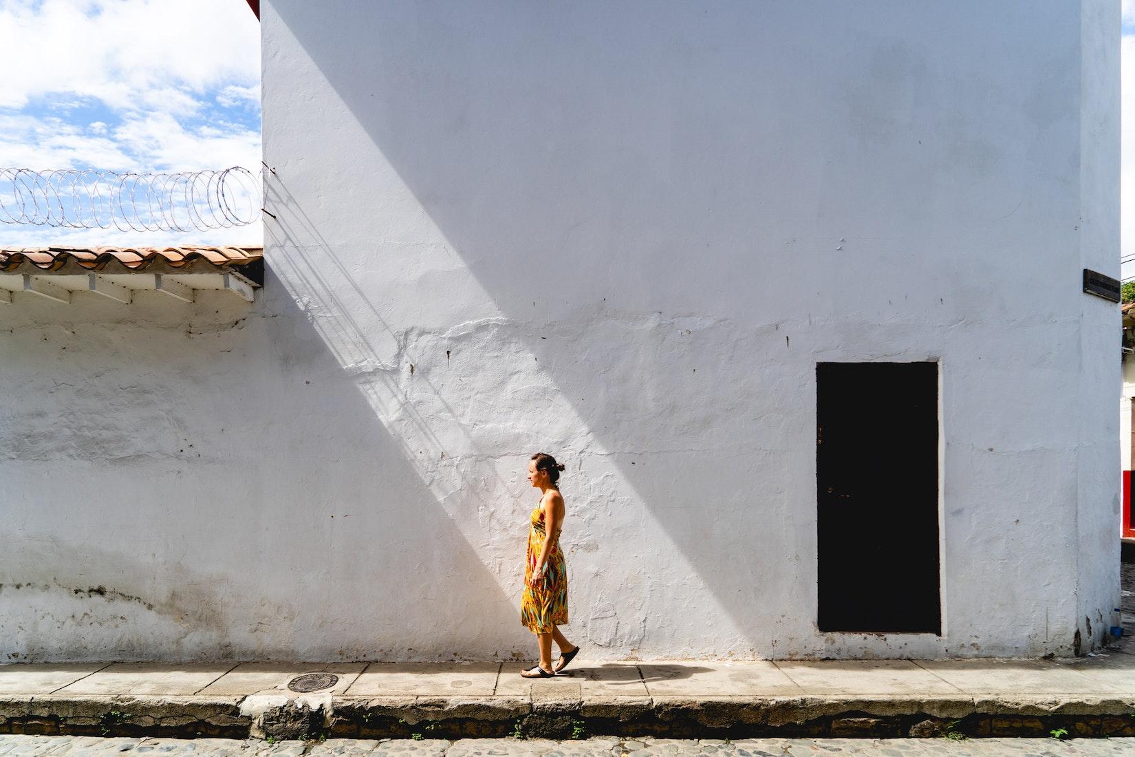 Girl walking between shadows on white walls