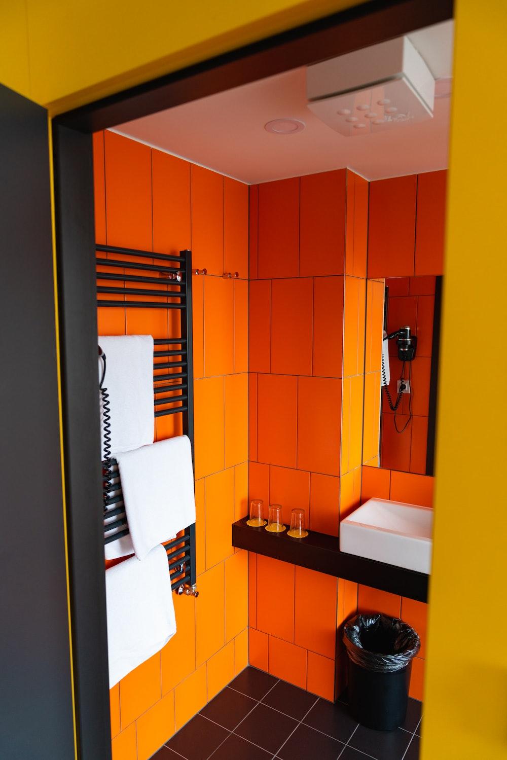 Orange-tiled bathroom at a MeetMe23 hotel room in Prague
