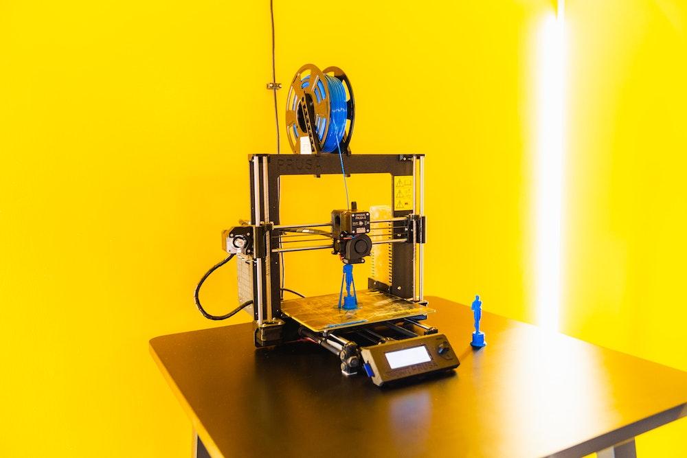 3D printer making small blue man statues in Meetme23 lobby