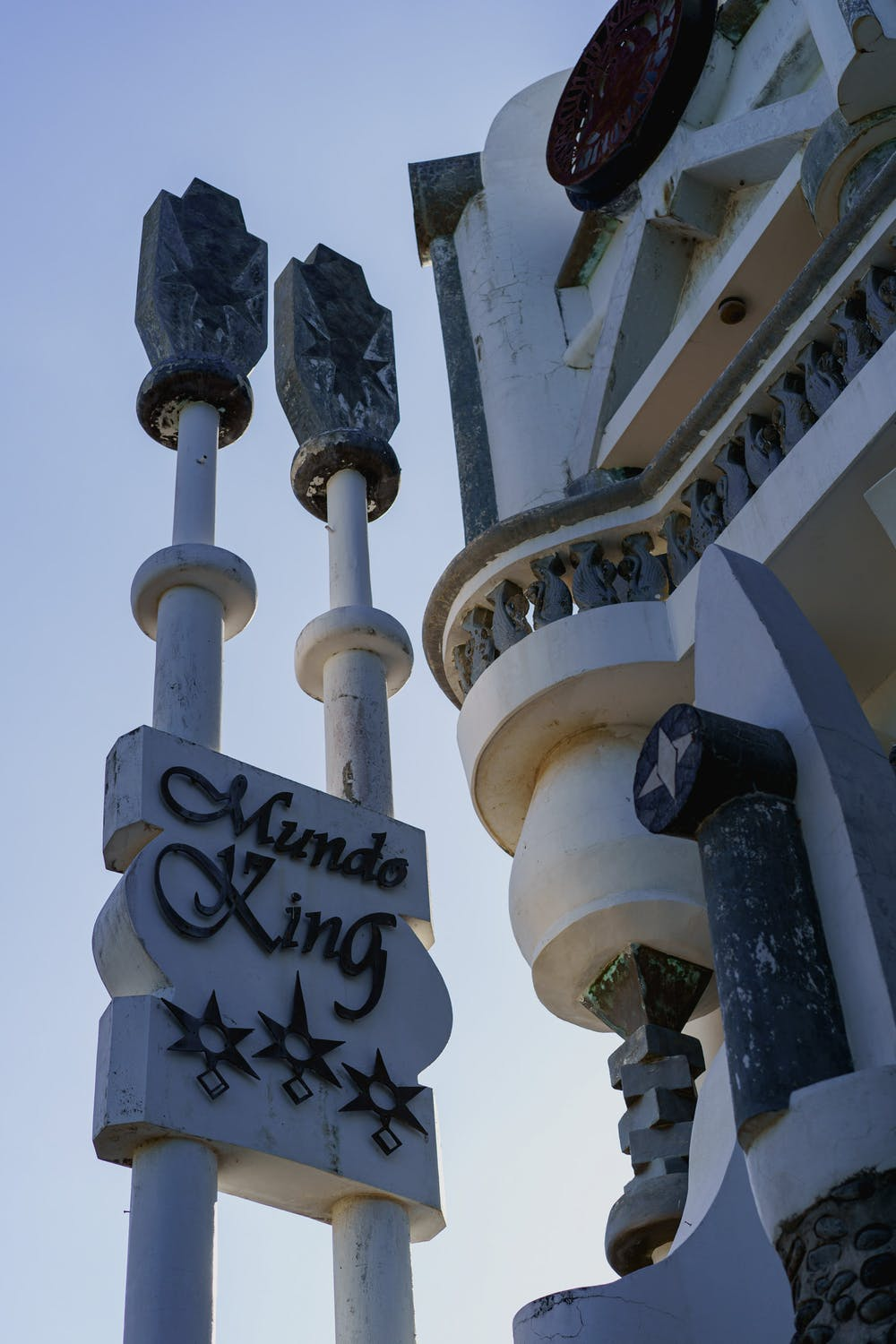 Mundo King sign on a white concrete pole against a blue sky