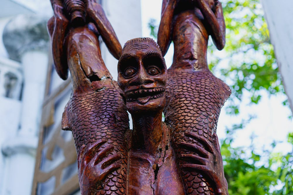 Creepy wooden carved Haitian statue of crazed man holding two mermaid bodies