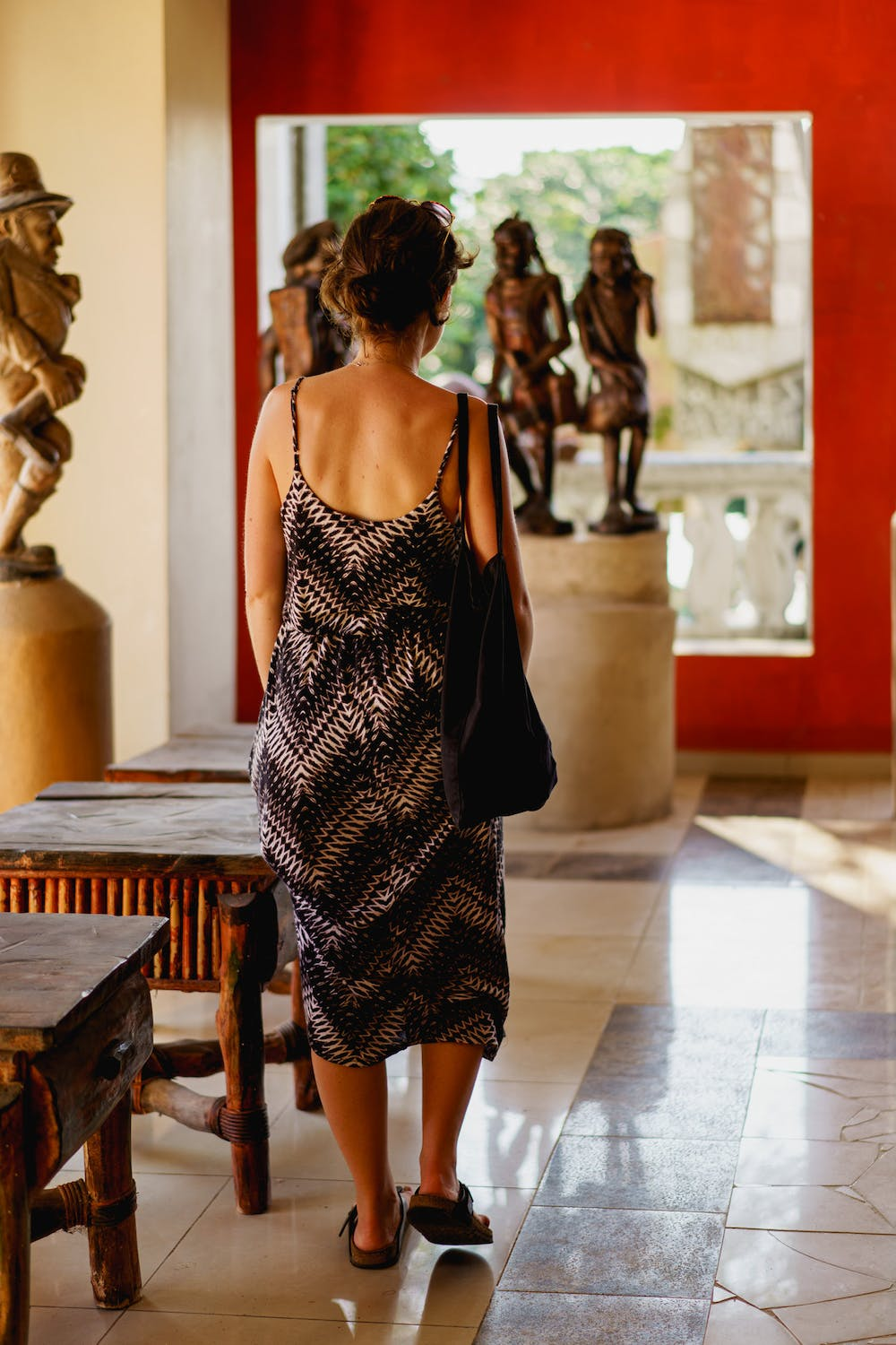 Girl in a dress walking in a hallway of Haitian wooden carving statues at Castillo Mundo King