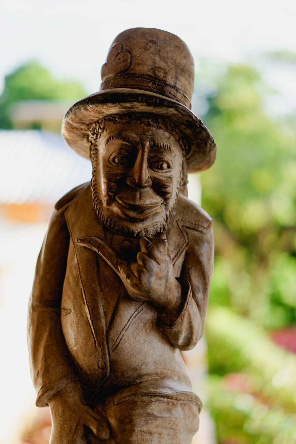 Haitian style wooden carved sculpture of a man wearing a top hat and a suit