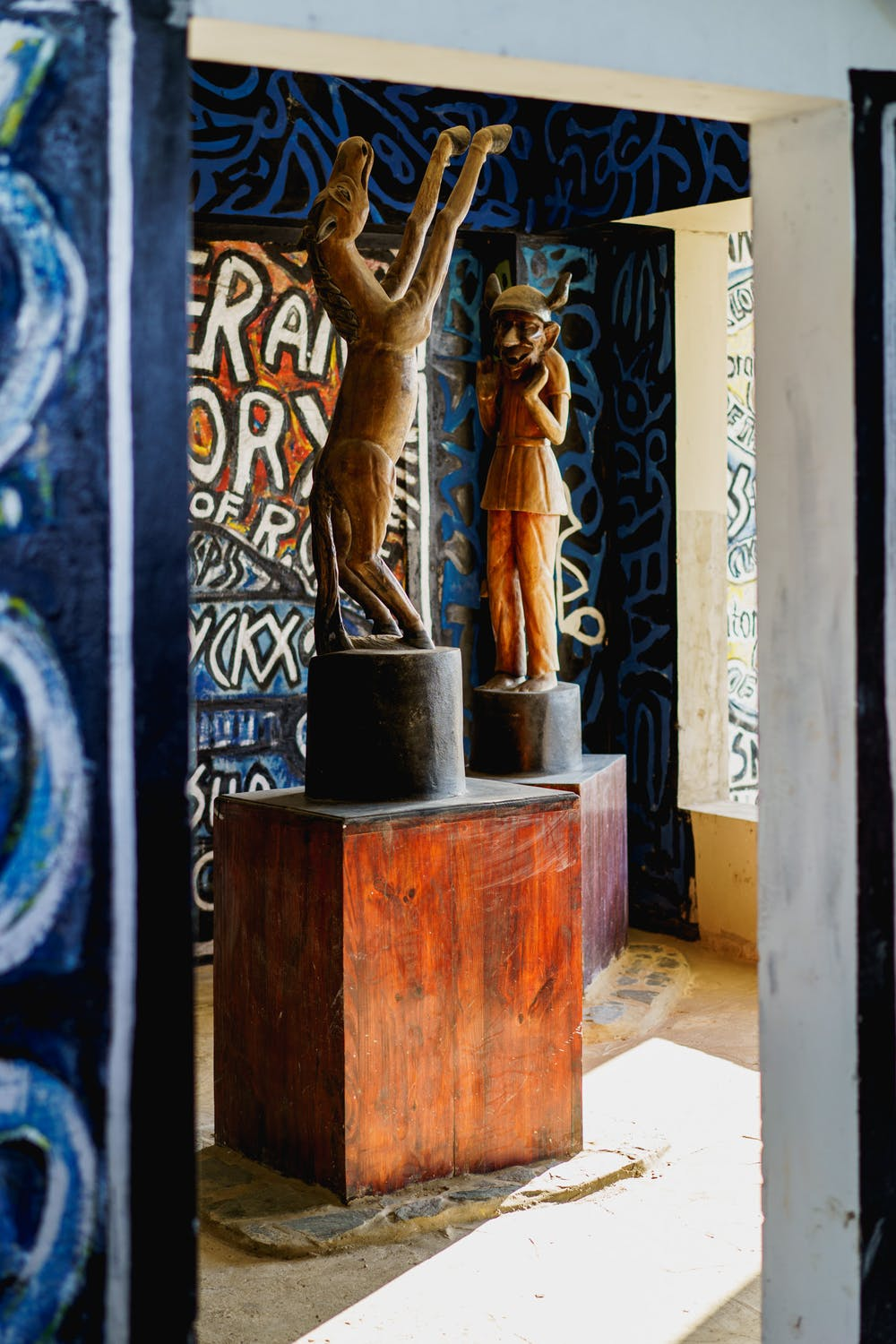 Wooden statues on pedestals in a open air room at Castillo Mundo King covered in wall art and hand painted murals