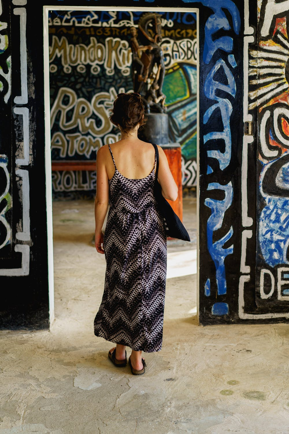 Girl walking through rooms covered in graffiti style painted wall art at Castillo Mundo King