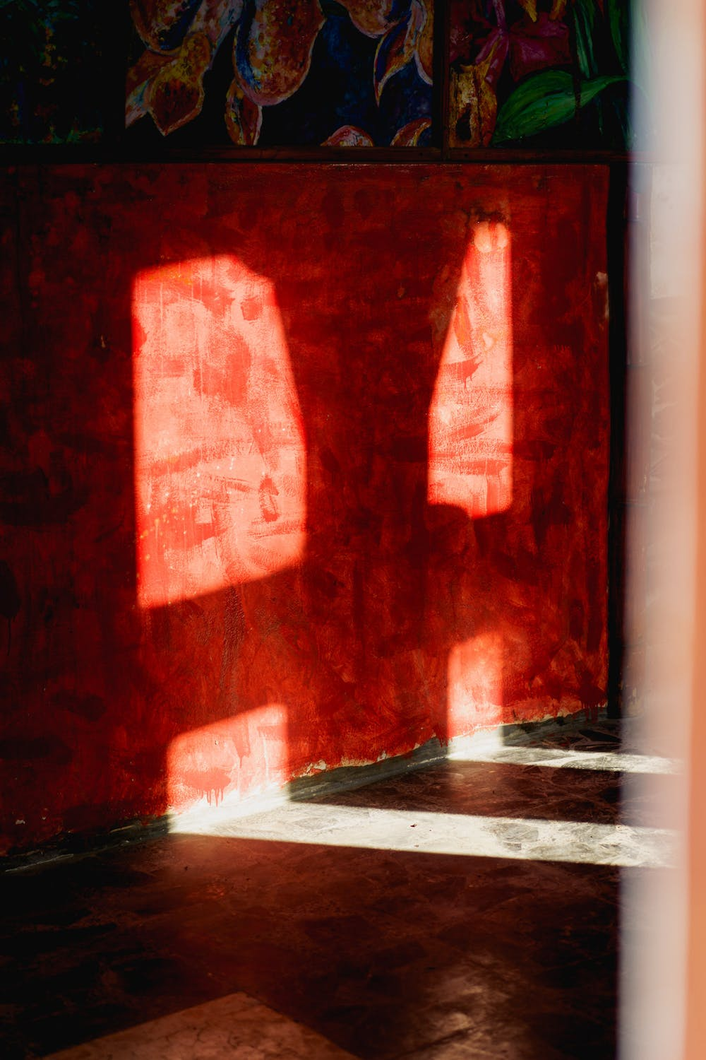 Shadows cast from light passing through concrete outlines against a red painted wall