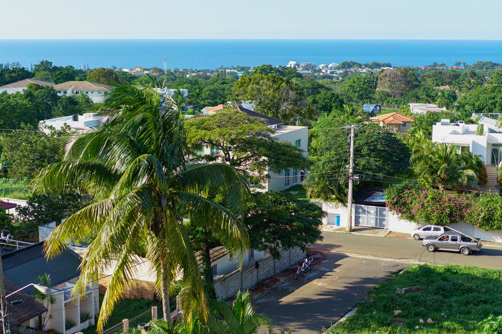 View of an upscale Dominican residential neighborhood in Sosua with a palm tree and view toward the Caribbean Sea