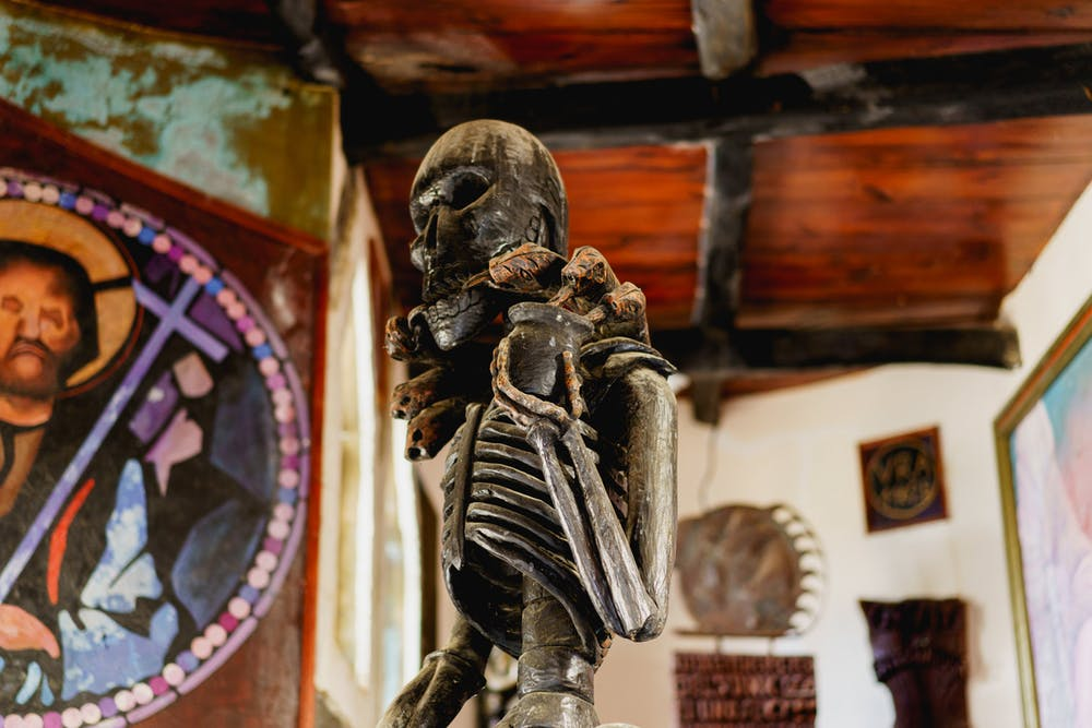Haitian statue carved from wood depicting a skeleton in a room filled with art and a Jesus painting