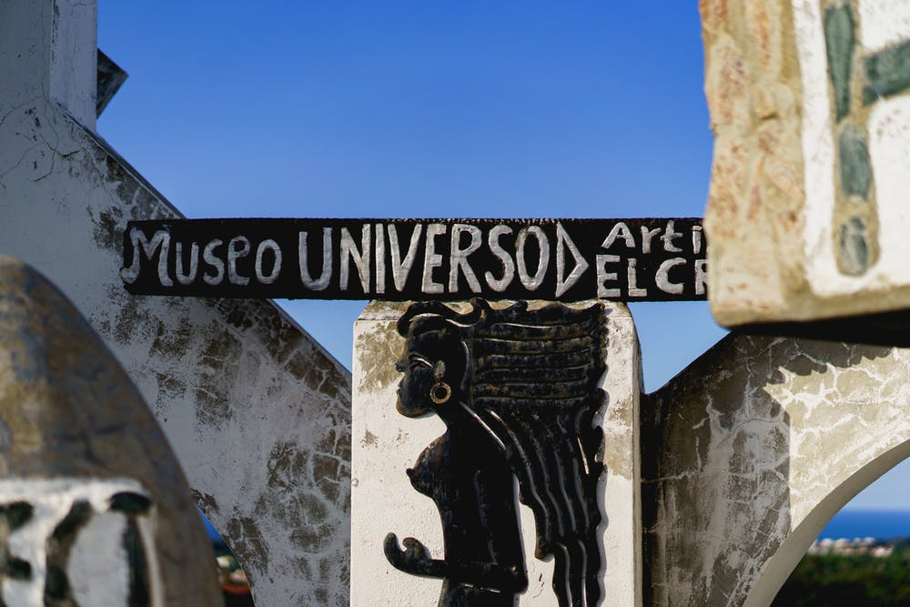 Museo Universo hand carved sign on white concrete at Castillo Mundo King against a perfect blue sky
