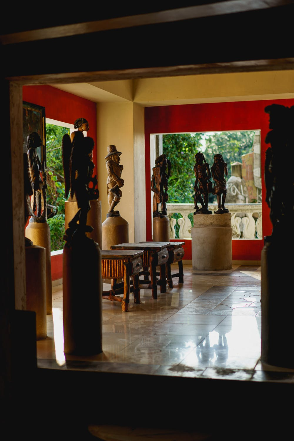 Room full of hand carved Haitian sculptures and statues in a open air room in the Castillo Mundo King mansion of Sosua