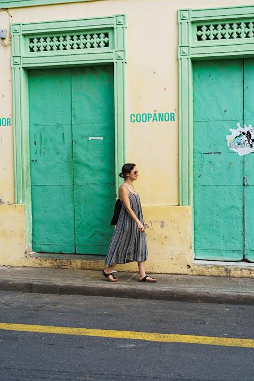 Puerto Plata şehrinin Dominik Cumhuriyeti'nin tarihi merkezinde pastel renkli duvarların ve kapıların yanından geçen kız