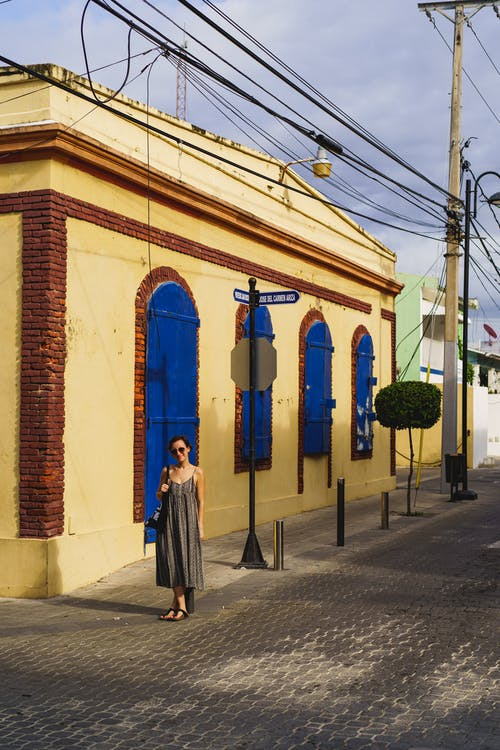 Puerto Plata Centro Historico Dominik Cumhuriyeti'nde sarı duvarları ve mavi kapıları olan kız