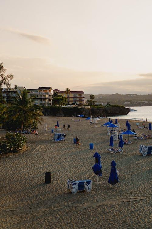 Sosua Dominik Cumhuriyeti'ndeki Playa Alicia'da gün batımı ve plaj kalabalığı