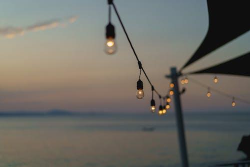 Sosua Dominik Cumhuriyeti'ndeki Waterfront Bar Playa Alicia'da gün batımı sırasında restoran çay ışıkları