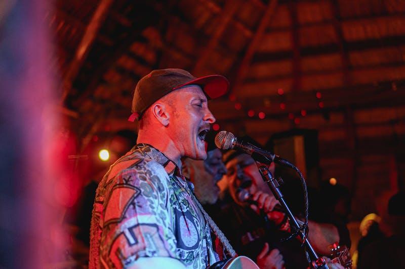 Açık mikrofon gecesinde şarkı söyleyen ve akustik gitar çalan adam La Chabola Cabarete Dominik Cumhuriyeti gurbetçi sahnesi