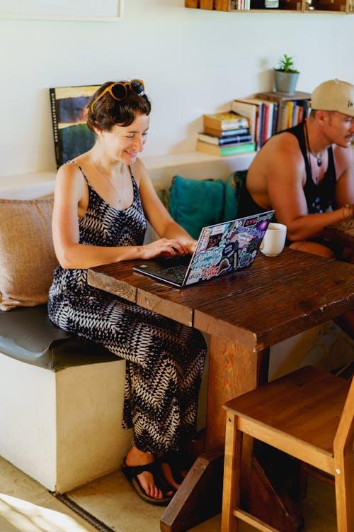 Popüler bir plaj kafede dizüstü bilgisayarla uzaktan çalışan kız