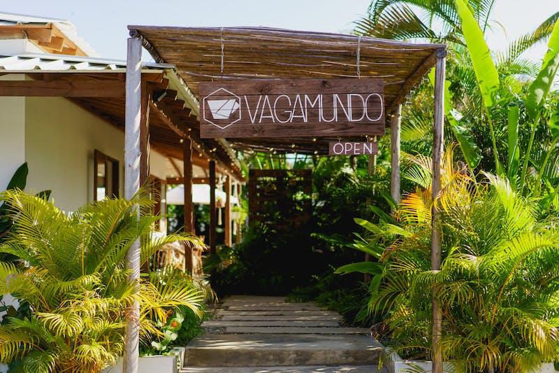 Yeşil tropik bitkilerle kaplı Vagamundo kafe tabelası ve giriş