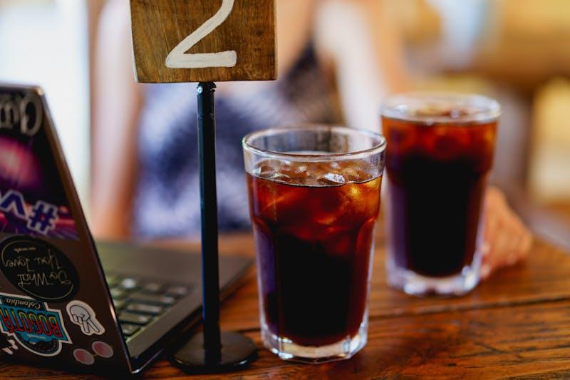 Bir dizüstü bilgisayarın yanında uzun bardaklarda iki buzlu soğuk demlenmiş kahve