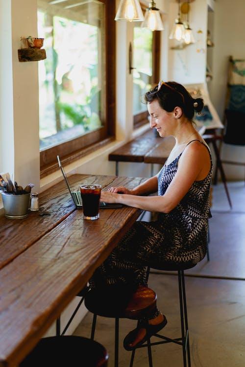 Pencerenin yanında bir bardakta buzlu kahve ile dizüstü bilgisayarda çalışan kız