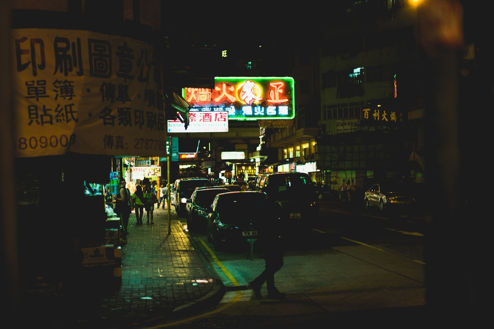 Looking down a street in Hong Kong at night with neon signs