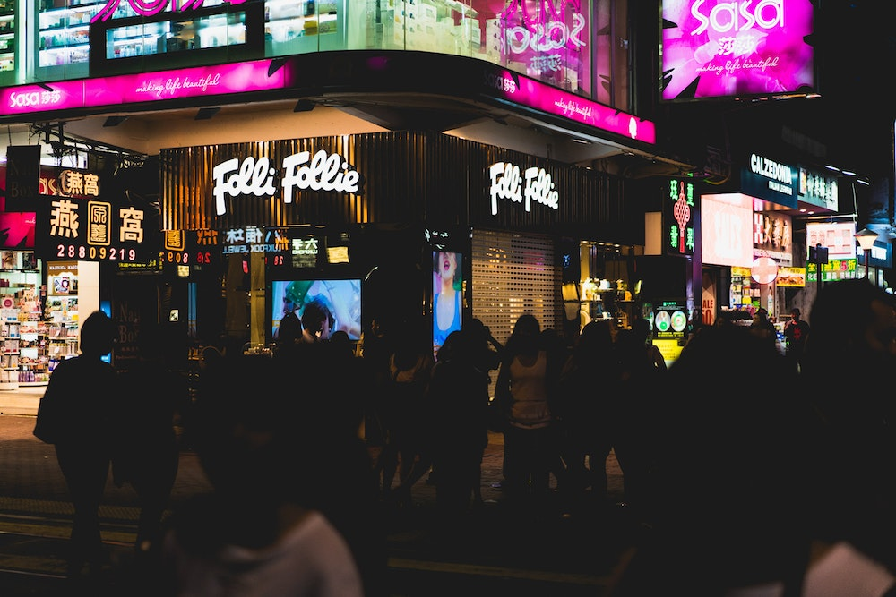 Neon signs behind a crowd of people on a busy street