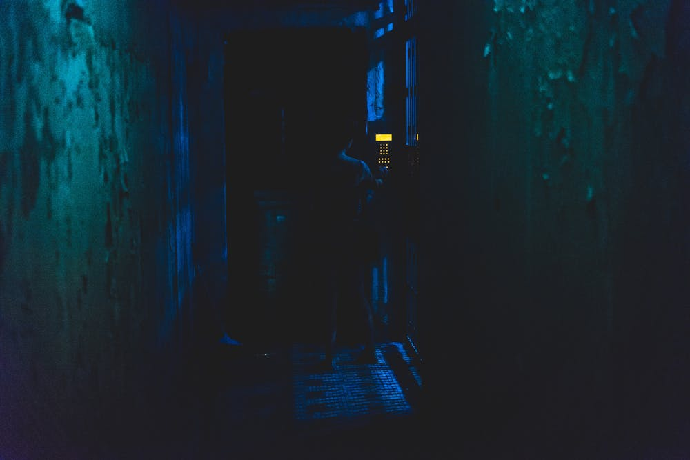 Dark narrow street alley at night showing a door entrance