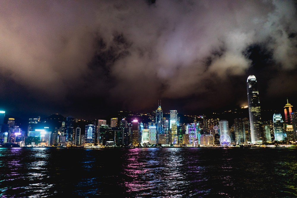 View of the colorful Hong Kong skyline at night with dark clouds