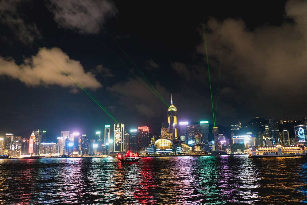 View of the colorful Hong Kong skyline at night with a lazer light show