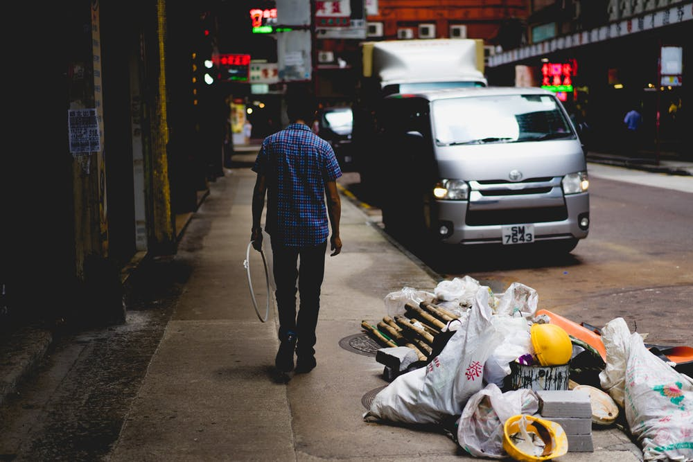 Man next to rubbish on the street on a Hong Kong Street