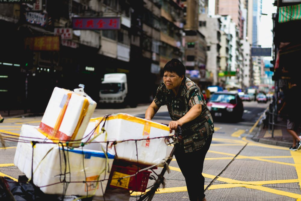 Woman pushing a cart of bins down the street