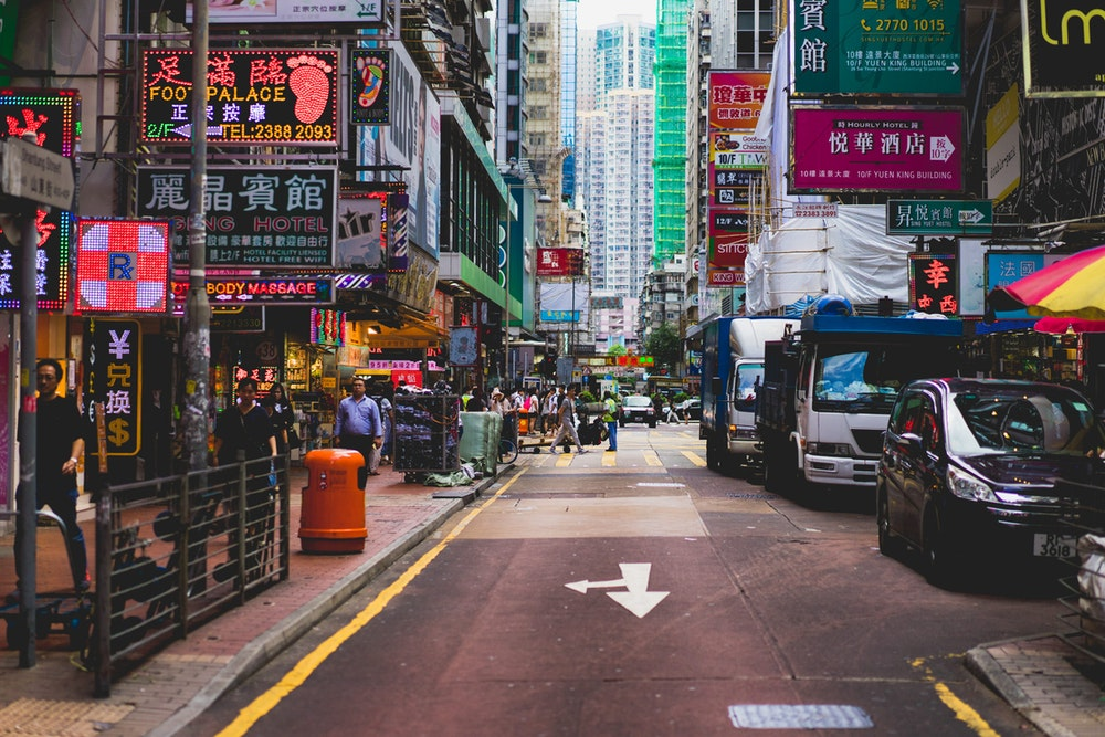 Busy street with cars, pedestrians and neon signs in Hong Kong