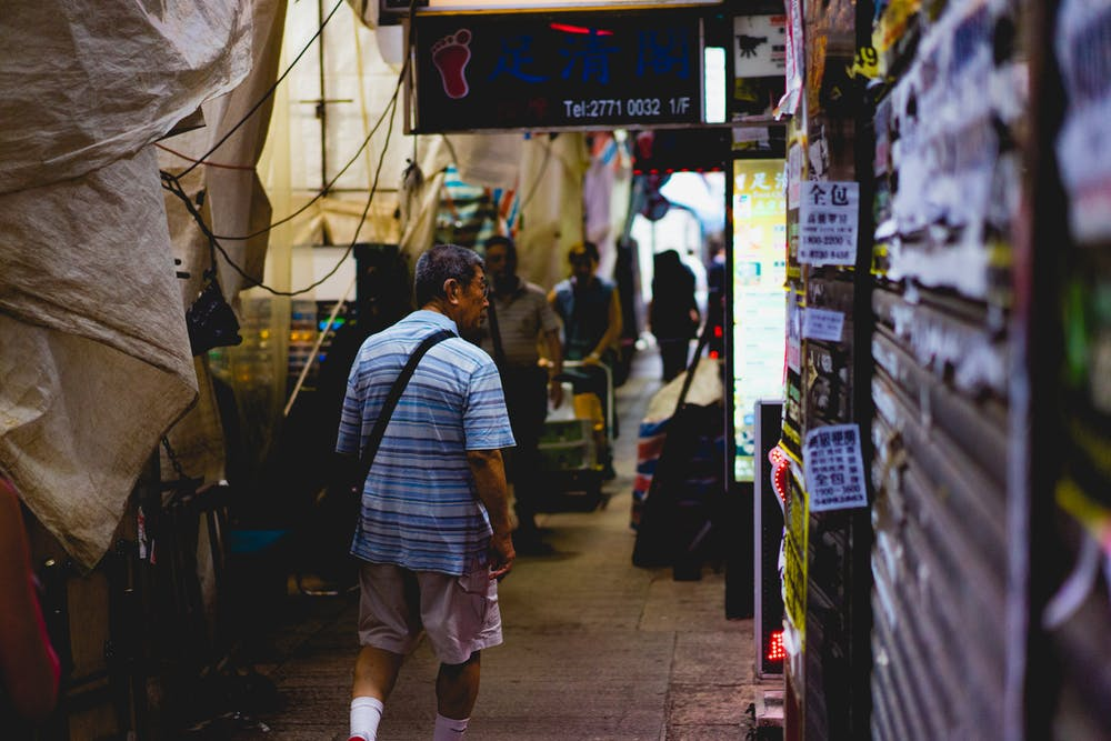 Man walking through a narrow market alley