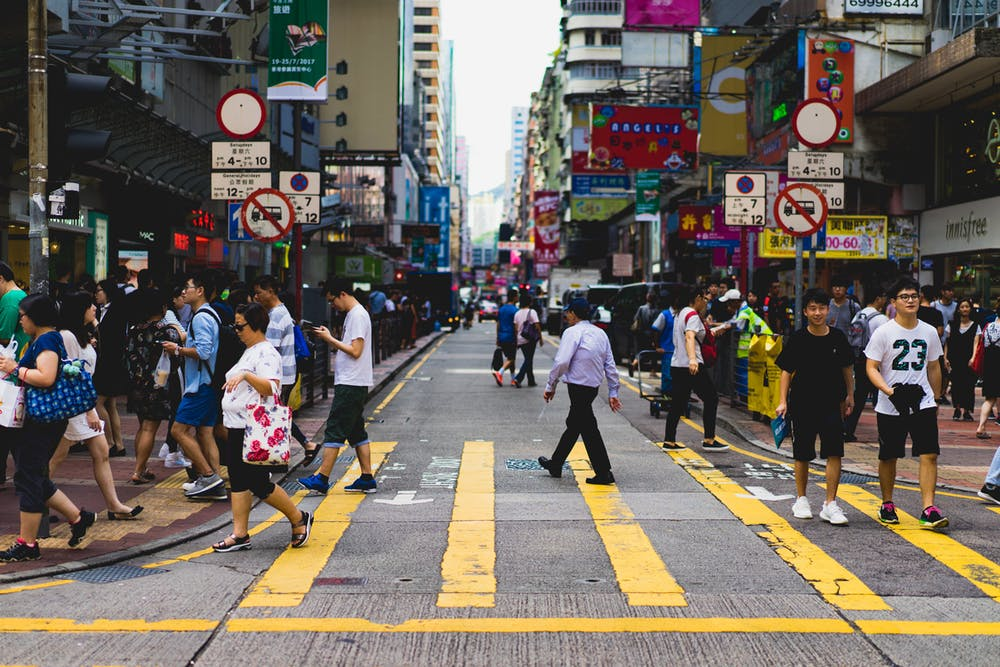People walking through a cross-walk in Hong Kong